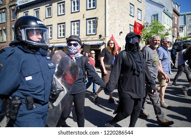 QUEBEC CITY-JUNE 9:  Protesters holding hands while walking and riot police keeping an eye on them during a rally to protest the G7 summit  on June 9  2018 in  Quebec City ,Canada