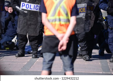 QUEBEC CITY-JUNE 9: A volunteer standing in front of the riot police  during a rally to protest the G7 summit  on June 9  2018 in  Quebec City ,Canada