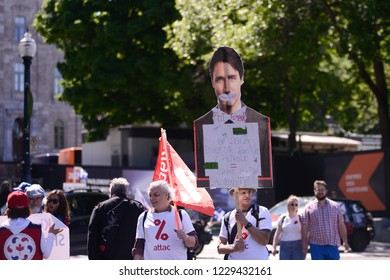 QUEBEC CITY-JUNE 9:Protesters walking with a a poster of Justin Trudeau  denouncing his environmental policies during a rally to protest the G7 summit  on June 9  2018 in  Quebec City ,Canada