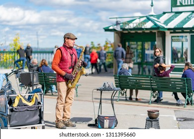 Quebec, OCT 1: Red cloth man playing saxophone under the Monument Samuel-De Champlain on OCT 1, 2018 at Quebec, Canada