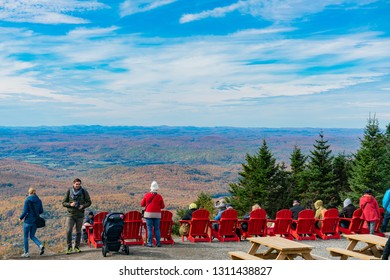 Quebec, OCT 3: Many people enjoying the natural senic of Mont-Tremblant National Park, sit on the red chair on OCT 3, 2018 at Quebec, Canada