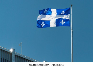 Quebec province flag waving in a blue clear sky.