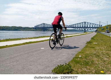 QUEBEC QC/CANADA MAY 31 2018 Cyclists on the Promenade Samuel de Champlain bike path in Quebec City, with the St Lawrence river at Pont du Quebec bridge beyond