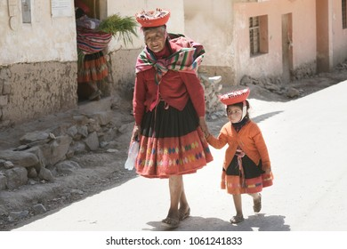 Quechua Indian Woman And Her Granddaughter Dressed In Colorful Handwoven Outfit. October 18, 2012 - Maras, Urubamba Valley, Peru
