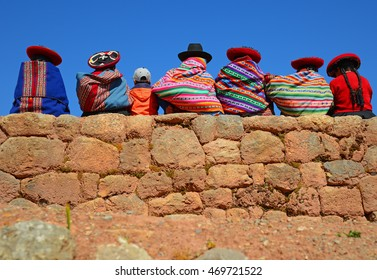 Quechua ladies and a young boy chatting on an ancient Inca wall, Peru.