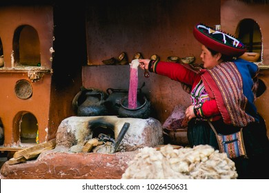 Quechua woman doing a demonstration of the process of natural dyed of the alpaca wool. Chinchero, Cusco, Perú. February 2018
