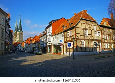 Quedlinburg, Germany - April 13, 2017: Street view in the center of ancient town with St. Nikolai gothic church in a sunny spring evening, Beauty of calm provincial life. Popular travel destination.