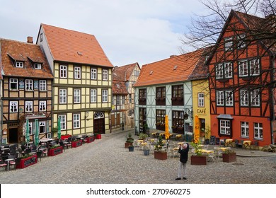 Quedlinburg, Germany - April 16, 2015: Tourist taking photograph of the colorful half-timbered houses on Schlossberg.