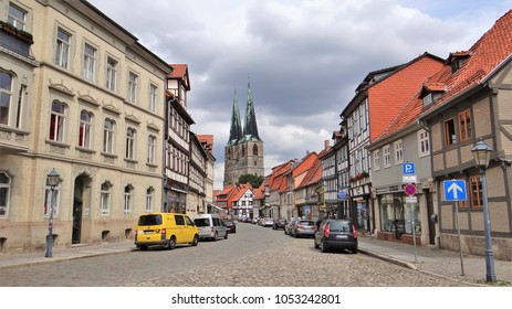 Quedlinburg / Germany - August 17 2017: Street with old buildings and a church in the medieval city Quedlinburg in the Harz