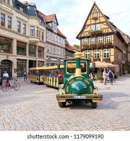 QUEDLINBURG, GERMANY – SEPTEMBER 08, 2018: Tourists during a city tour through the Old Town of Quedlinburg with a locomotive
