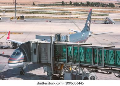 Queen Alia Airport, Amman, Jordan - May 19, 2018 A Royal Jordanian aircraft stands on the passenger passageway before taking off in Queen Alia Airport, Amman