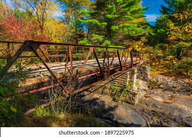 Queen Elizabeth II wildlands provincial park Kawartha lakes county Ontario Canada featuring bridge, cascade, pond and forest in autumn on a sunny day