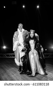The queen sits on the throne, the king stands. Black and white photo. Theater. Scene. Shine.