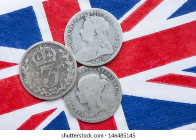Queen Victoria three silver threepences from the 19th century (from 1873, 1891, 1898) on a British flag. The coins have been in circulation. Concept for history of British Empire or collecting coins.