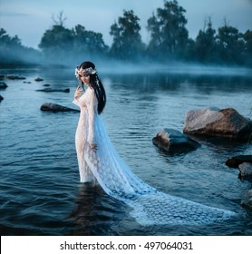 queen in a vintage dress, standing in water looking at sinking plume among large stones in water.A wreath made of shells, handmade.Foggy forest.Mystical photo shoot.Fashionable toning.