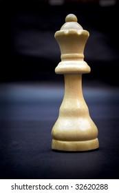 Queen, wooden chess piece on dark background.