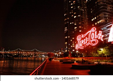 Queens, NY - September 20 2015: View of the Pepsi Cola sign and the waterfront promenade at Gantry Plaza State Park at night