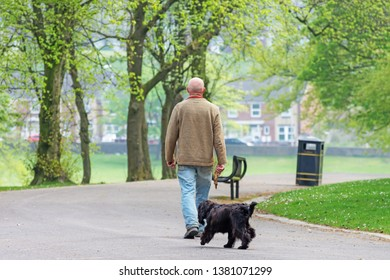 Queens Park Blackburn, Lancashire/England - 24.04.2019 - Man enjoying walking his dog in the park