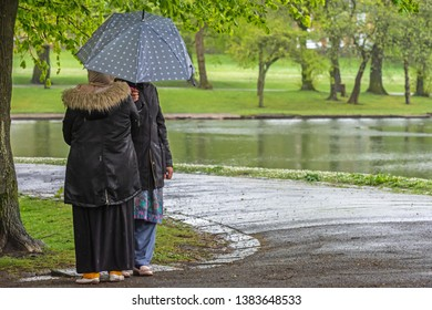 Queens Park Blackburn, Lancashire/England - 29.04.2019 - Two Asian ladies sheltering under their umberella from the stormy weather