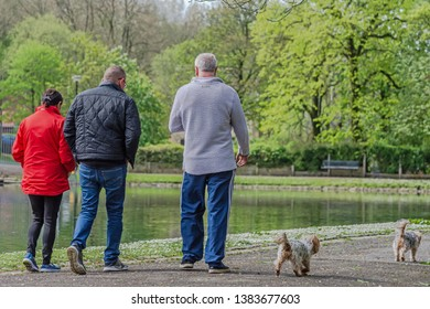 Queens Park Blackburn, Lancashire/England - 29.04.2019 - Group of people out walking their dogs in the park