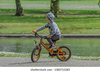 Queens Park Blackburn, Lancashire/England - 29.04.2019 - Young boy on his new bike posing for his parents