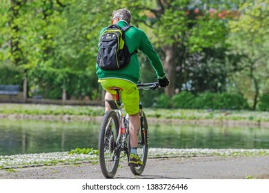 Queens Park Blackburn, Lancashire/England - 29.04.2019 - Man wearing green fleece jacket and rucksack riding his bicycle in the park