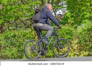 Queens Park Blackburn, Lancashire/England - 29.04.2019 - Man wearing gray fleece jacket gray pants and rucksack riding his bicycle in the park