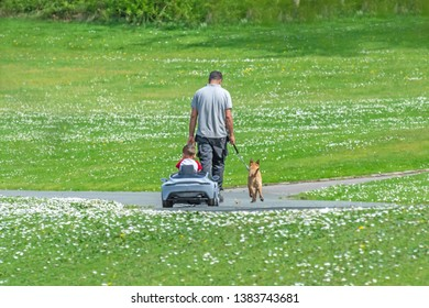 Queens Park Blackburn, Lancashire/England - 29.04.2019 - Adult male walking his dog followed by small child in toy pedal car