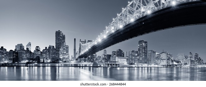 Queensboro Bridge over New York City East River black and white at night with river reflections and midtown Manhattan skyline illuminated.