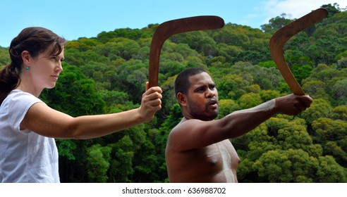 QUEENSLAND, AUS - APR 17 2016: Yirrganydji Aboriginal warrior man teach woman tourist how to throw a boomerang in Queensland, Australia.