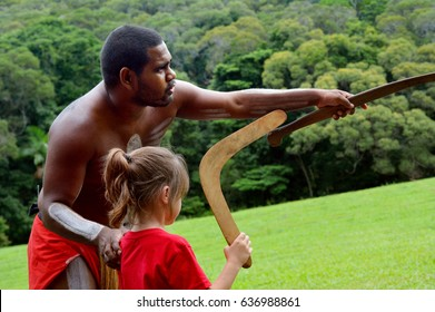 QUEENSLAND, AUS - APR 17 2016: Yirrganydji Aboriginal Australians man teaches a young girl (Talya Ben-Ari age 06) how to throw a boomerang in Queensland, Australia.