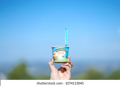 Queensland, Australia - April 15, 2018 : A photo of a hand holding up the cup of Ben and Jerry's ice cream in caramel cheesecake flavor. Editorial use only.