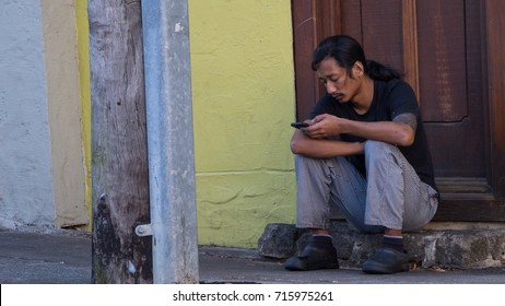 QUEENSLAND, AUSTRALIA - AUGUST 26, 2017 : Unidentified man uses his smartphone while he is waiting for something besides Gordon St, Milton