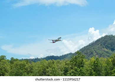 Queensland, Australia – December 11, 2014: A Qantas plane, above the rain forest hills, leaving Cairns in Tropical North Queensland, Australia. Qantas Airways is the third oldest airline in the world
