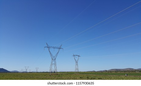 QUEENSLAND, AUSTRALIA - JULY 14, 2018: High voltage power electric pole line with Melons field and sky at Rapisarda farms, Australia.