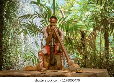 Queensland, Australia- March 16, 2018:Aborigine actor performs music with traditional didgeridoo musical instrument in the Tjapukai Culture Park in Kuranda, Queensland, Australia