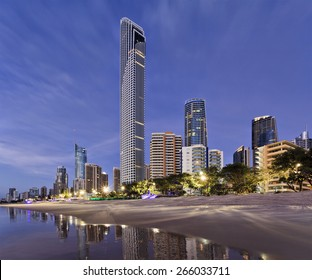 Queensland's gold coast landmark waterfront with tall modern skyscrapers reflecting in still beach waters at sunrise