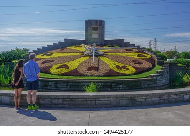 Queenston, Ontario / Canada - August 14, 2019: A couple views the Niagara Parks Floral Clock. The floral design is changed twice each year.