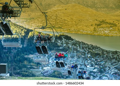 QUEENSTOWN, NEW ZEALAND - APRIL 17, 2019: Fun rider tourists take cable chair lifts for Skyline Luge, most popular activity on April 17, 2019 in Queenstown, South New Zealand.