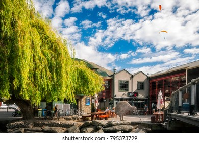 Queenstown, New Zealand -December 23, 2017: People enjoying a beautiful morning Queenstown wharf pier restaurants. Queenstown alpine city is well known for wonderful scenery and adventure sports.