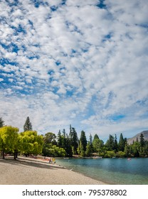 Queenstown, New Zealand -December 23, 2017: Beautiful morning at lake Wakatipu beach in Queenstown, with the Queenstown Gardens in the background.