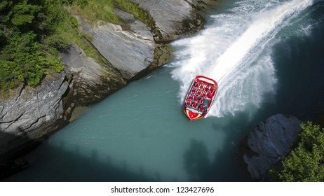 QUEENSTOWN, NEW ZEALAND - DECEMBER 28: Tourists enjoy a high speed jet boat ride on the Shotover River on December 28, 2012 in Queenstown, New Zealand. Queenstown is a popular summer resort.