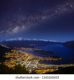 Queenstown, New Zealand. Night cityscape as seen from the Queenstown gondola. Composite with the Milky Way over the Remarkables mountain range