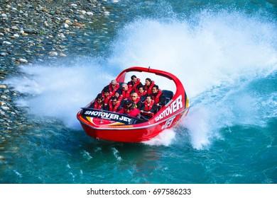 QUEENSTOWN, NEW ZEALAND - November 18: Tourists enjoy a high-speed boat ride on Queenstown's Shotover river on November 18, 2014 in Queenstown, New Zealand. Queenstown is a popular alpine resort