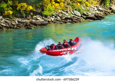 QUEENSTOWN, NEW ZEALAND - November 18: Tourists enjoy a high-speed boat ride on Queenstown's Shotover river on November 18, 2014 in Queenstown, New Zealand. Queenstown is a popular alpine resort