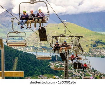 QUEENSTOWN, NEW ZEALAND/DEC. 13, 2018: Riders in a gondola lift enjoy spectacular views of the city, Lake Wakatipu, and surrounding mountains as they ascend Bob's Peak on a cloudy day early in summer.