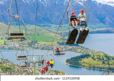 Queenstown, NZ – April 15, 2018: Fun riders on a steep cable chair lift carrying them and their carts up to the top of hill slope for a luge ride with beautiful views of Lake Wakatipu and Queenstown.