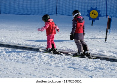 Queenstown NZ August 2018 two girls riding magic carpet ski lift to top of beginners learning slope