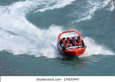 QUEENSTOWN, NZ - JAN 18 2014:Tourists enjoy a high speed jet boat ride on the Shotover River in Queenstown, New Zealand. Queenstown is one of the most popular summer and winter resort in NZ.