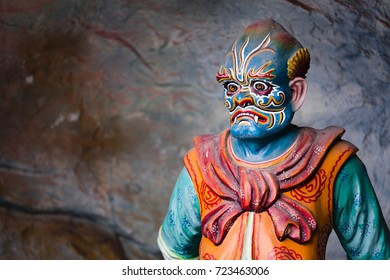"Queenstown, Singapore - December 29, 2015: A sculpture of Hu Fa Shi Zhe, a creature of the chinese mythology responsible for the laws of the ""Ten Courts  of Hell"" at the Haw Par Villa, in Singapore."
